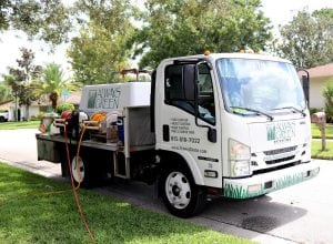 always green truck parked curbside while providing lawn care